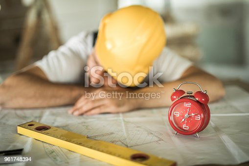 Manual worker taking a nap on blueprints at construction site. Focus is on alarm clock.
