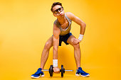 It's too hard for me! Full length, legs, body, size portrait of youth man look at camera can not lift dumbbells from the floor isolated on vivid yellow background
