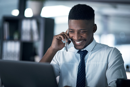 Shot of a young businessman talking on a cellphone while working on a laptop in an office at night