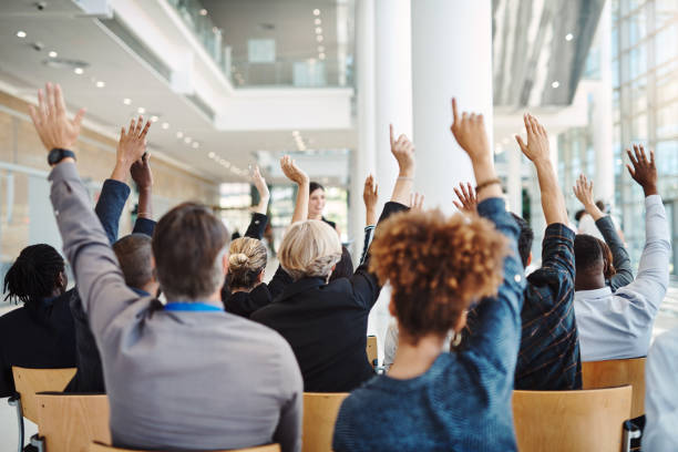 It's up to you to learn something new Rearview shot of a group of businesspeople raising their hands to ask questions during a conference faq stock pictures, royalty-free photos & images