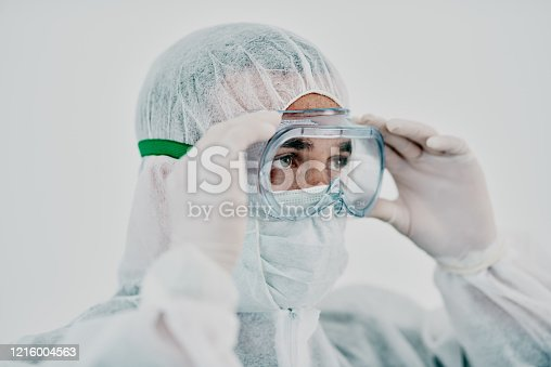 Shot of a young man putting on his protective gear before the decontamination process
