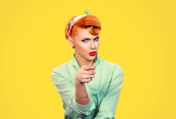 It's you! Portrait angry annoyed pin up retro style woman getting mad pointing finger at you camera showing hand gesture this is you, you chosen, isolated on yellow wall background.  Negative emotions stock photo