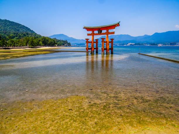 Itsukushima Floating Torii Gate in Miyajima, Japan Miyajima, Japan - May 26, 2015: View of the Itsukushima Floating Torii Gate during low tide. shinto stock pictures, royalty-free photos & images