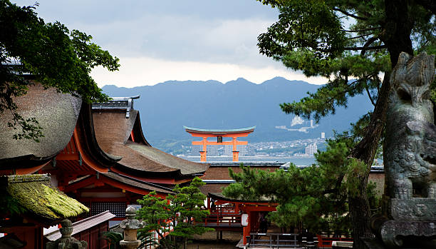 Itsukushima Shinto shrine on Miyajima in Japan Hatsukaichi, Japan - August 5, 2013: Itsukushima Shinto shrine and the famous Torii gate on Miyajima in Japan. The shrine is situated at the beach of Hatsukaichi city on the island Itsukushima, better known as Miyajima. UNESCO World Heritage Site. The island Miyajima is situated near the coast of Hiroshima city and is a popular travel destination for japanese as well as foreign tourists. itsukushima shrine stock pictures, royalty-free photos & images