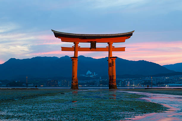 Itsukushima Shrine at low tide on Miyajima island, Japan Miyajima island, Japan - June 16, 2010: View of Itsukushima Shrine at low tide on Miyajima island, Japan. The Itsukushima Torri gate is one of the most sacred and visited sites of Japan. itsukushima shrine stock pictures, royalty-free photos & images