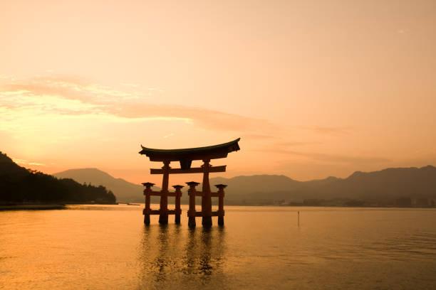 Itsukushima shrine, Miyajima Island, Japan Miyajima, Japan - October 29, 2009: Sunset with Red c shrine, Miyajima Island, Japan. The shrine complex is listed as a UNESCO World Heritage Site. torii gate stock pictures, royalty-free photos & images