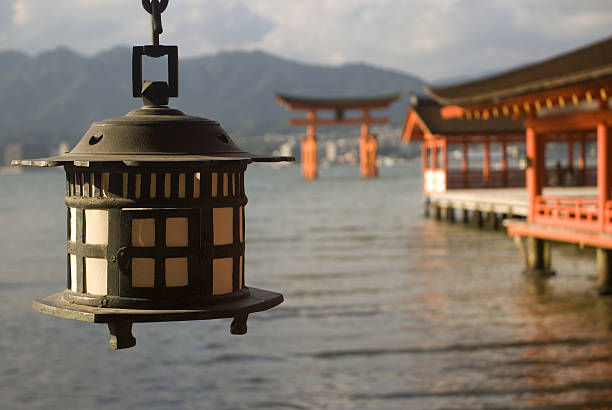 Itsukushima Shrine, Miyajima, Japan Miyajima, Japan - October 26, 2013: Itsukushima Shrine is one of the most important Shinto shrine in Japan. The island of Miyajima where it is located is still a holy place. The wooden gate of the shrine stands in the sea during high tide, but stays dry during low tide. itsukushima shrine stock pictures, royalty-free photos & images