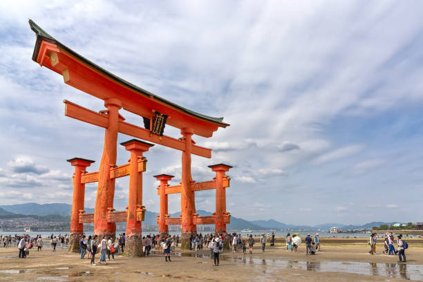 Itsukushima Shrine torii gate during low tide, Japan Miyajima, Japan - April 27, 2014: View of Itsukushima Shrine torii gate during low tide with tourists walking under it. This shrines is one of Japan's most popular tourist attractions itsukushima shrine stock pictures, royalty-free photos & images