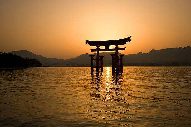 Itsukushima Torii Gate Miyajima, Japan - May 3, 2008: View of MIyajima's famous Torii Gate at Itsukushima Shrine on a calm afternoon. This shinto shrine was erected in the 6th century, but the present structure dates from the mid-16th century, and the Torii gate dates from 1875. itsukushima shrine stock pictures, royalty-free photos & images