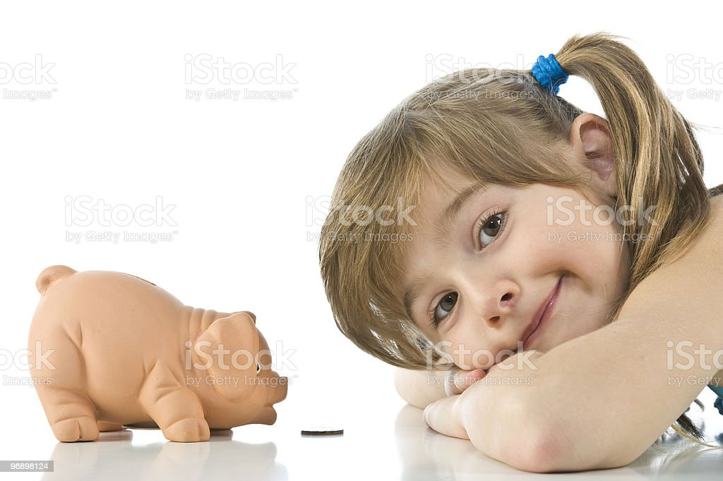 ittle girl depositing change in her piggy bank royalty-free stock photo