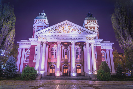 """Ivan Vazov National Theatre illuminated at night – Sofia, Bulgaria  The Ivan Vazov National Theatre (Bulgarian: Народен театър """"Иван Вазов"""", Naroden teatar """"Ivan Vazov"""") is Bulgaria's national theatre, as well as the oldest and most authoritative theatre in the country and one of the important landmarks of Sofia, the capital of Bulgaria. It is located in the centre of the city, with the facade facing the City Garden. Founded in 1904 by the artists from the Salza i Smyah company, it was initially called simply the National Theatre, but before being named after the prominent writer Ivan Vazov it also bore the name of Krastyu Sarafov between 1952 and 1962. Incidentally Vazov's play,"""