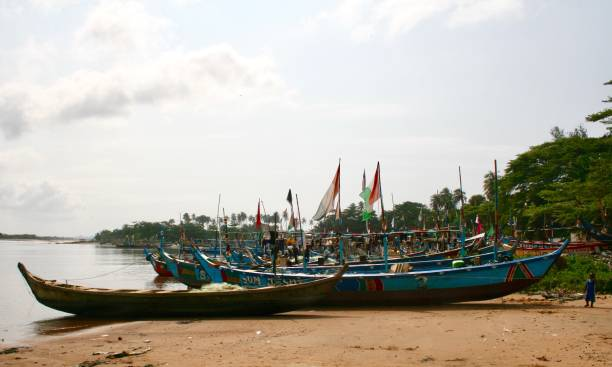 Ivorian boats on the beach Fishing boats on the beach after work. The picture was taken on Sassandra beach when boats were back on the beach. It shows boats with flags. côte d'ivoire stock pictures, royalty-free photos & images