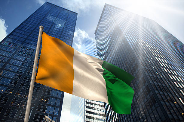 Ivory coast national flag Ivory coast national flag against low angle view of skyscrapers côte d'ivoire stock pictures, royalty-free photos & images