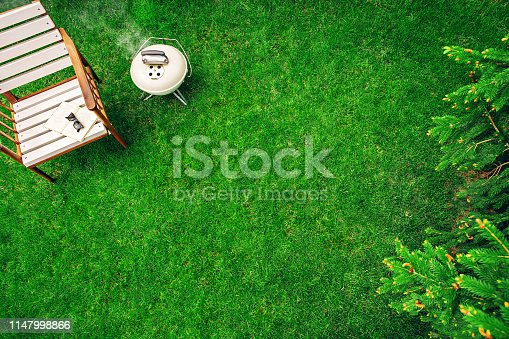 istock Ivory colored grill on the grass near the wooden armchair with a book and glasses. Top view 1147998866