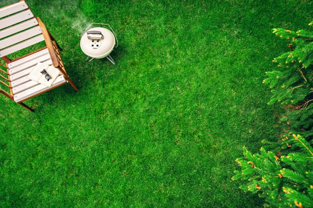 象牙色的烤架放在木制扶手椅附近的草地上, 配有一本書和一杯眼鏡。頂視圖 - 前後院 個照片及圖片檔