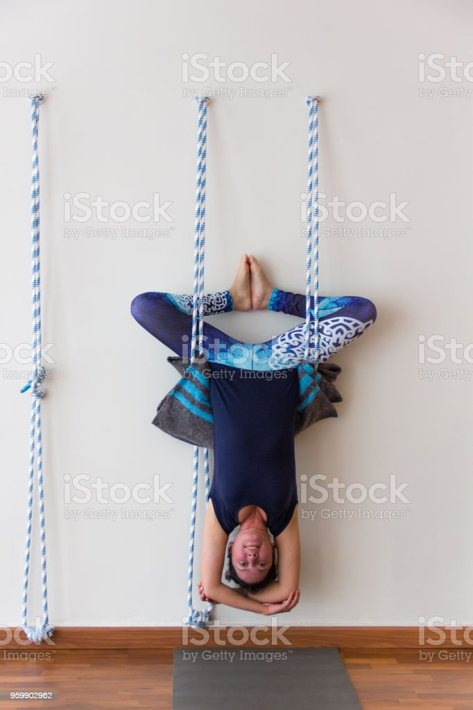 Iyengar Yoga Practitioner Hanging Upside Down From Ropes On White