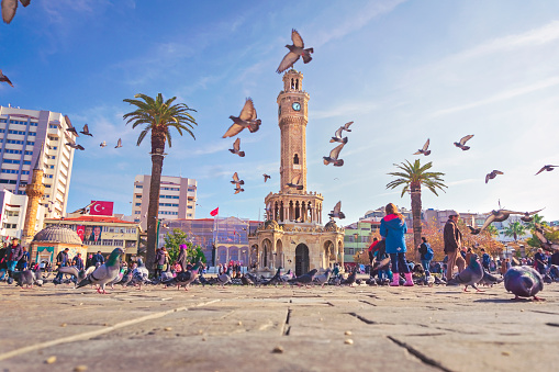 Izmir, Turkey - December 1, 2018: Doves flying near historical clock tower, it was built in 1901 and accepted as the symbol of Izmir City. Konak Square with walking ordinary people