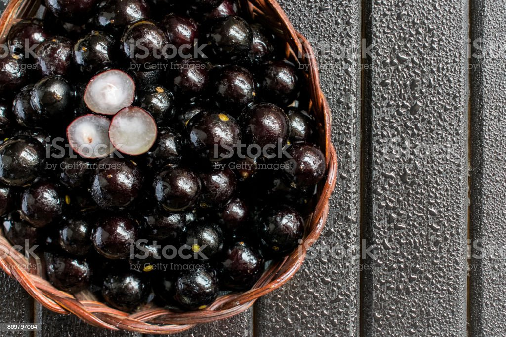 Jabuticabas, also known as Brazilian Berry or Brazilian Grapetree (Plinia cauliflora) fruits on a wooden vine basket, with a black wooden background wet with water drops stock photo
