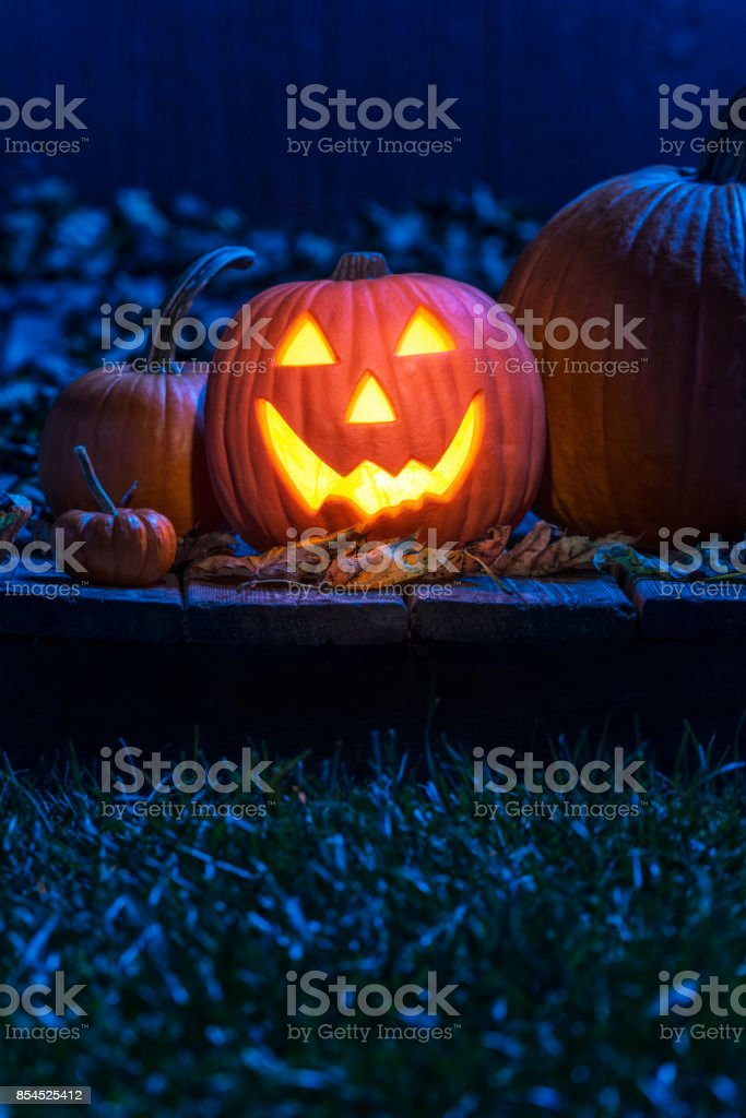 Jack O' Lantern and pumpkins sitting on old wooden porch in the moon light stock photo