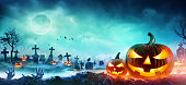 istock Jack O' Lanterns And Zombie Hands Rising Out Of A Graveyard In Misty Night 1032548124