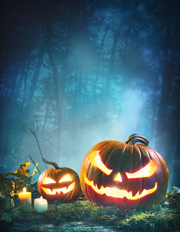 Jack o' lanterns glowing at moonlight in front of spooky forest. Halloween Background