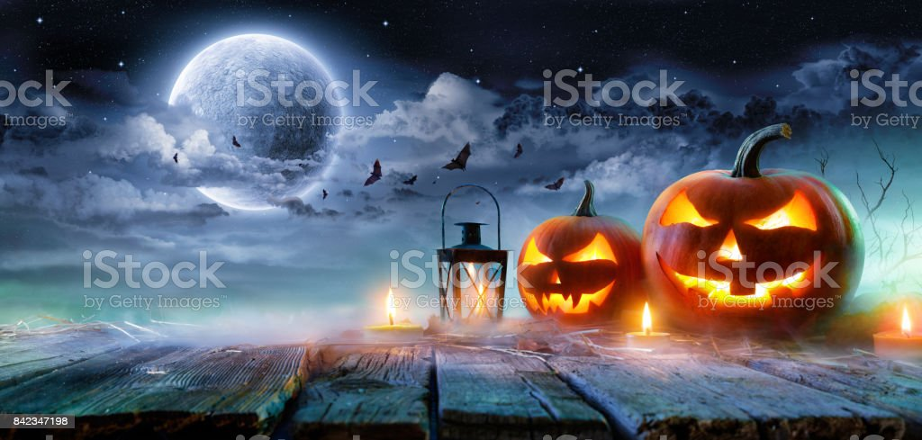 Jack o ' linternas brillando a la luz de la luna en la noche Spooky - escena de Halloween - foto de stock