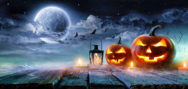 jack o' lanterns glowing at moonlight in the spooky night - halloween scene - halloween стоковые фото и изображения