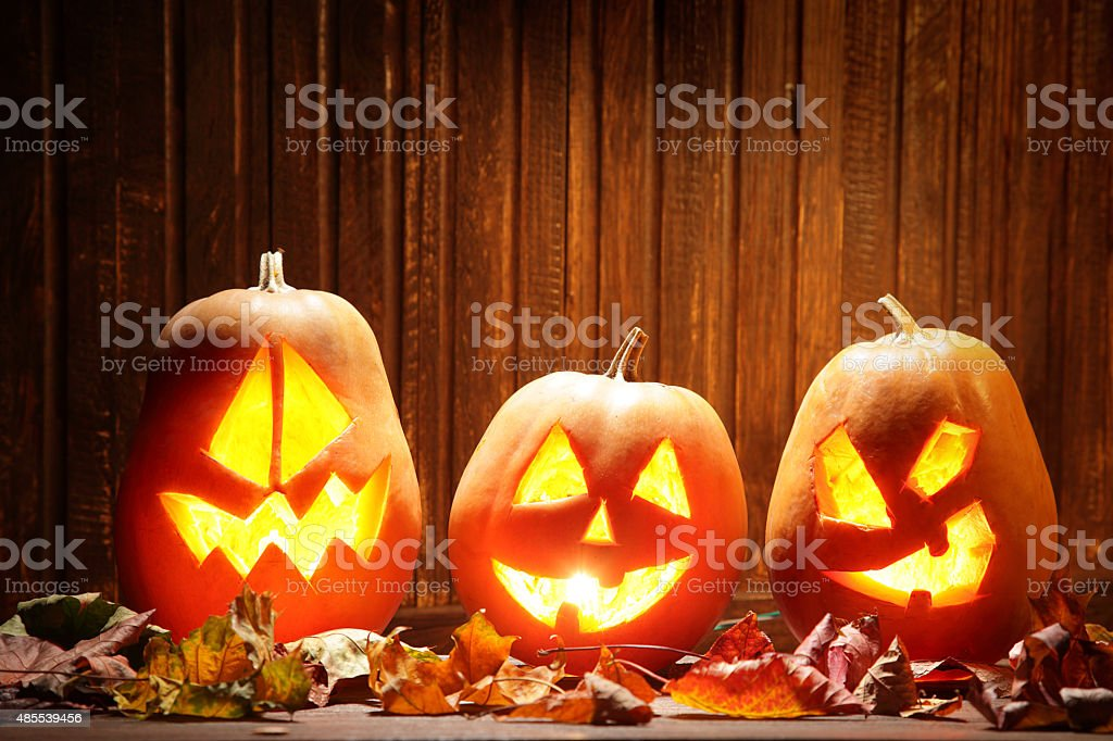 Jack o lanterns  Halloween pumpkin face on wooden background stock photo