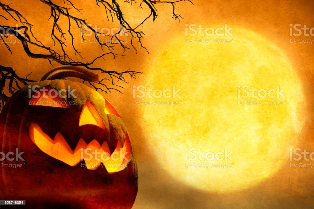 Jack O'Lantern In Front Of Barren Tree And Full Moon stock photo