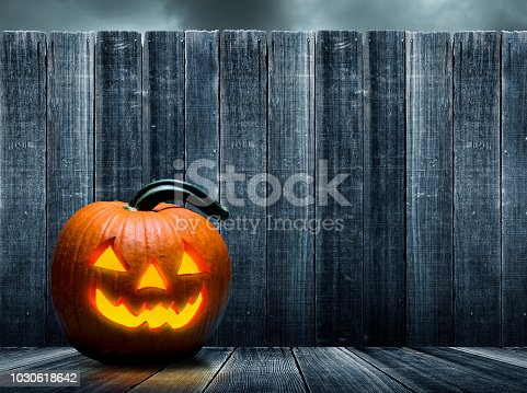 An illuminated jack o'lantern rests on a porch in front of an old weatheres fence that provides ample room for copy and text.