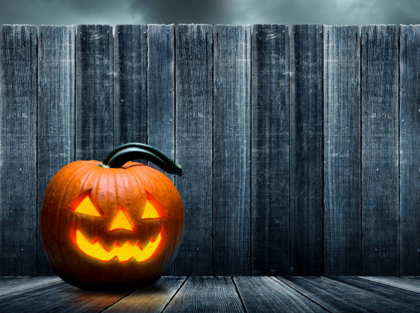 Jack O'Lantern Sits On Porch In Front Of Old Weathered Fence stock photo