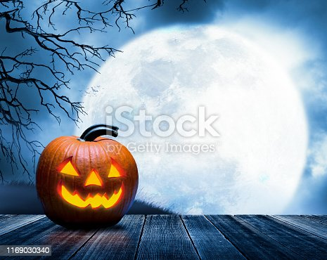 An illuminated jack o'lantern rests on a porch in front of a large full moon that rises over a small grassy hill  framed by the bare branches of a tree.