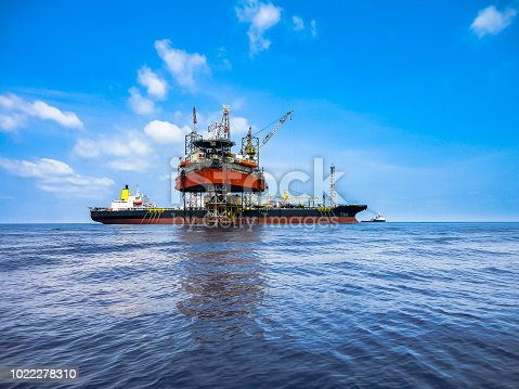 Jack up drilling rig on oil well platform with FPSO ship on site with beautiful cloudy blue sky in offshore oil field