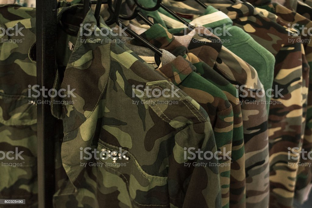Jacket military style hanging on clothes rack. stock photo