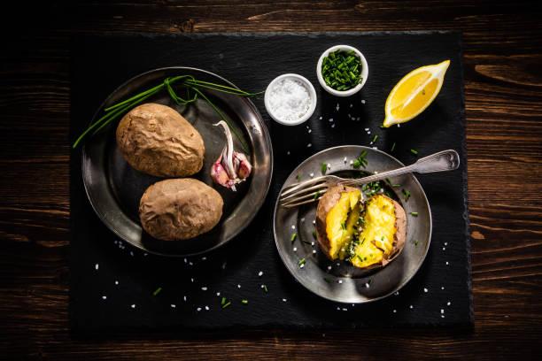 Jacket potatoes on black stone board stock photo