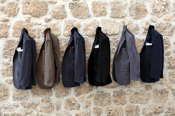 jackets hanging on wall - menswear stock photos and pictures