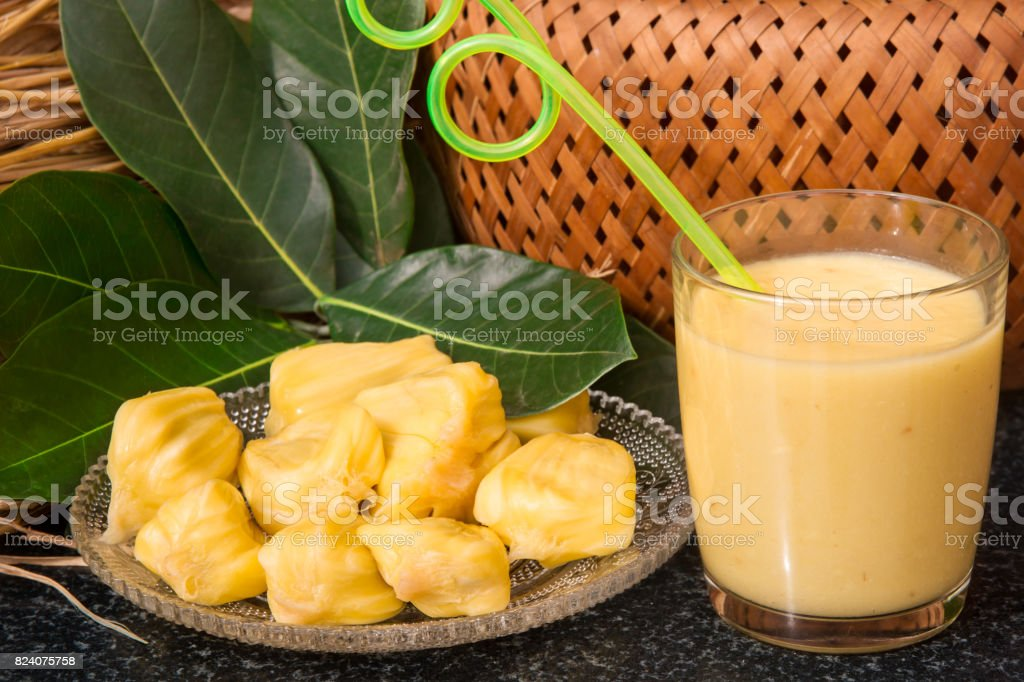 Jackfruit juice in a glass. Fresh sweet jackfruit slices on a glass plate. stock photo