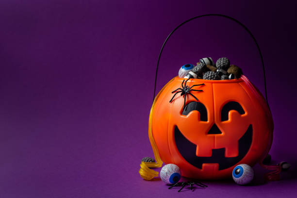 Jack-o-lantern bag full of candy on a purple background with copy space, horizontal stock photo