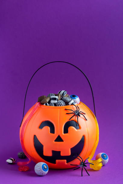 Jack-o-lantern bag full of candy on purple background with copy space,  vertical stock photo