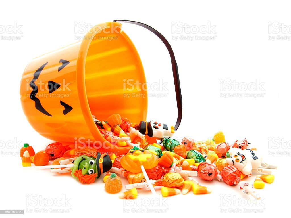 A jack-o-lantern bucket full of candy tipped over  stock photo