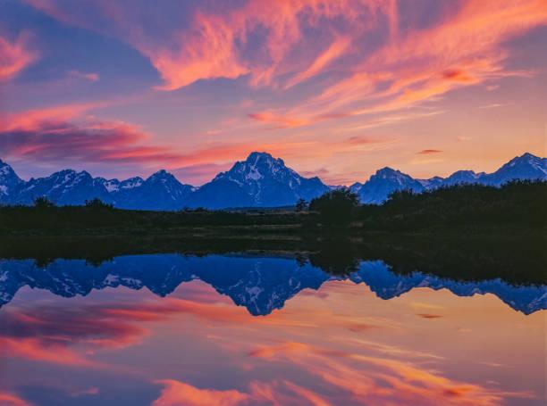 Jackson Lake glows in pink sunset at Grand Teton National Park stock photo