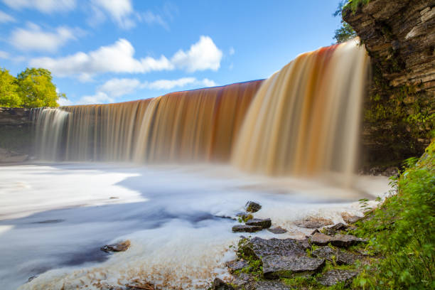 Jagala is the biggest waterfall in Estonia. Long exposure day shot. Close up. Water is red due to swamp organics. stock photo
