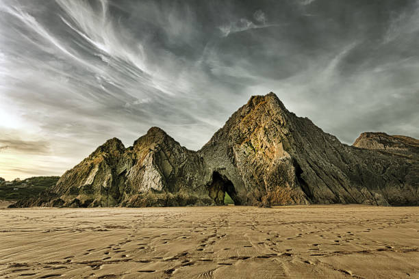 Jagged and dramatic Three Cliffs Bay Dramatic sky over the monolithic Three Cliffs on the Gower peninsula, a landmark beach and a haven for rock climbers. south wales stock pictures, royalty-free photos & images