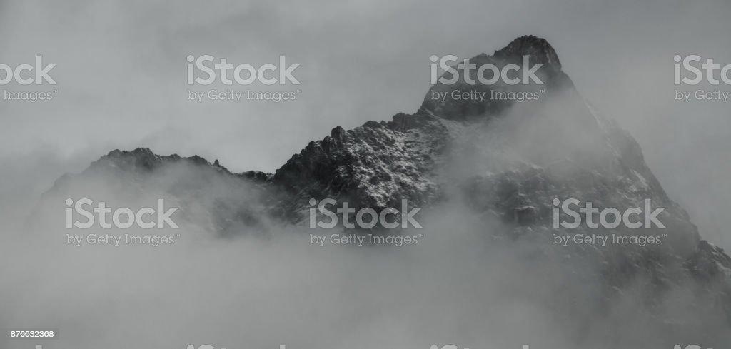 jagged mountain ridge in mist and fog stock photo