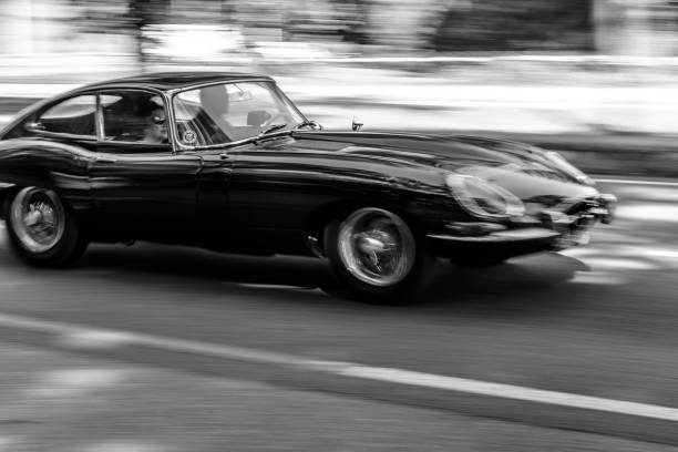 Jaguar E-Type driving at high speed on a road through a forest stock photo