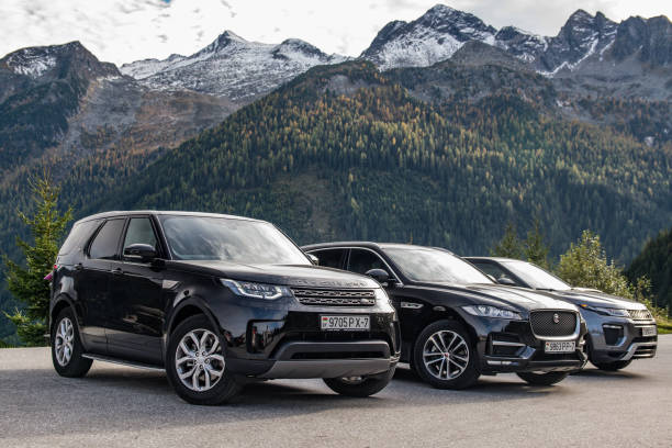Jaguar F-Pace, Land Rover Discovery 5 and Range Rover Evoque Salzburg, Austria - October 2, 2017: Jaguar F-Pace, Range Rover Evoque and Land Rover Discovery 5 made a long way to a mountain pass Umbrail in Switzerland. Photo taken on a parking lot in the Alps near Salzburg. The Jaguar F‑Pace is a performance SUV that combines maximum driving exhilaration with efficiency. Land Rover Discovery 5 is a modern British off-road car which is more SUV in its 5th generation. Range Rover Evoque is a compact British SUV. jaguar car stock pictures, royalty-free photos & images