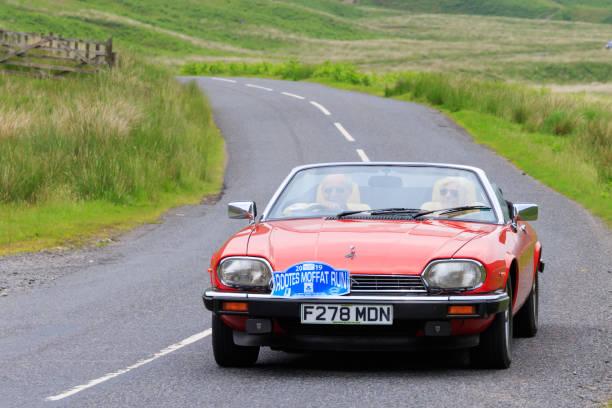 Jaguar Moffat, Scotland - June 29, 2019: 1988 Jaguar XJS sports car in a classic car rally en route towards the town of Moffat, Dumfries and Galloway jaguar xj stock pictures, royalty-free photos & images