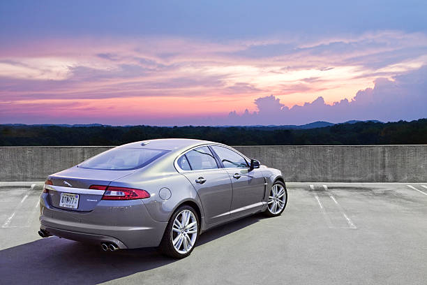 Jaguar XF Nashville, USA - June, 15th 2010: A 2010 Jaguar XF Supercharged on top of a parking garage during sunset. jaguar car stock pictures, royalty-free photos & images