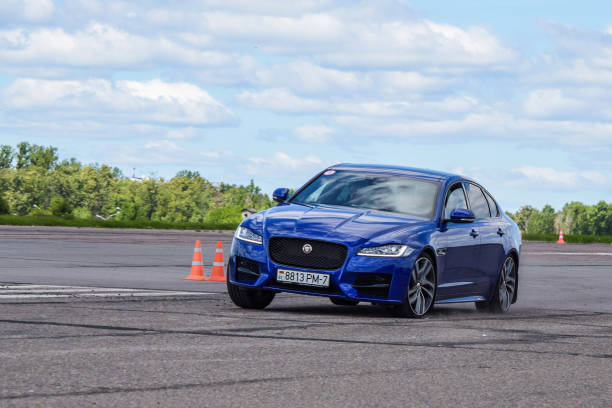 Jaguar XF Minsk, Belarus - July 7, 2017: Blue Jaguar XF sedan drives on a handling track during test drives. Jaguar XF is a luxury business saloon with distinctive design, dynamic drive and state-of-the-art technologies. Thanks to Jaguar's Lightweight Aluminium Architecture, XF is more efficient, offers lower running costs, and reduces emissions. jaguar car stock pictures, royalty-free photos & images