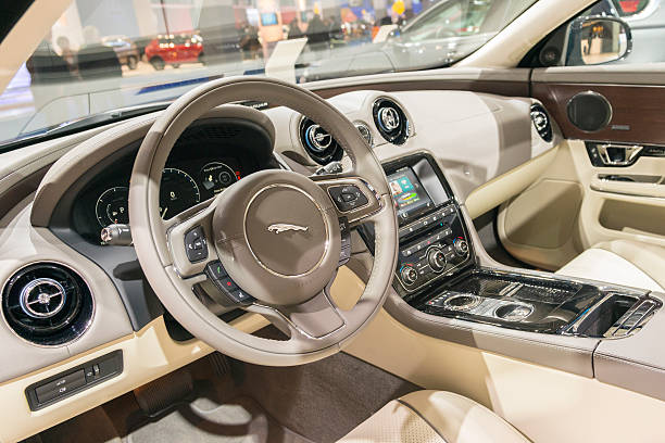 Jaguar XJ luxury saloon car interior Brussels, Belgium - Januari 12, 2016: Interior of a Jaguar XJ luxury saloon car front view. The car is fitted with leather seats, wooden panels and a large information display on the dashboard. The new XJ features an innovative, all-LCD dashboard and console displays. The car is on display during the 2016 Brussels Motor Show. jaguar xj stock pictures, royalty-free photos & images